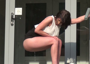 Attractive brunette lady in front of her fr-enemy's door