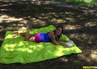 Redhead beauty gives a curious blowjob outdoors at a picnic