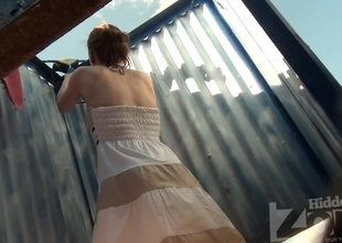 Magnificent girl in pretty attire undressing in the cabin